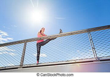 Sporty woman doing stretching exercises outdoors