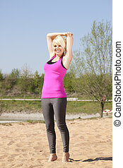 Sporty woman doing stretching on the beach