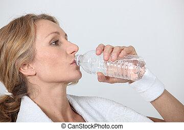 Sporty woman drinking bottle of water