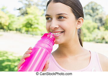 Sporty woman drinking water