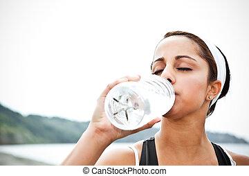 Sporty woman drinking water - A beautiful asian woman...