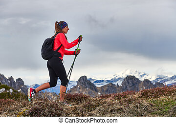 Sporty woman during a trek in the mountains alone