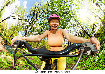 Sporty woman holding on handlebar of her bike