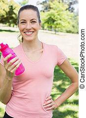 Sporty woman holding water bottle in park