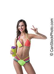 Sporty woman in bright bikini posing with shaker