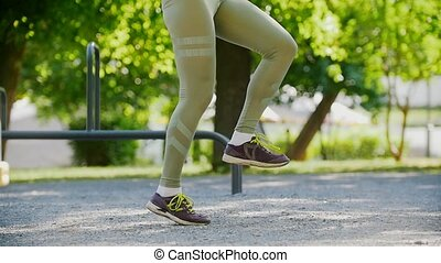 Sporty woman in leggings and purple sneakers jumping rope in...