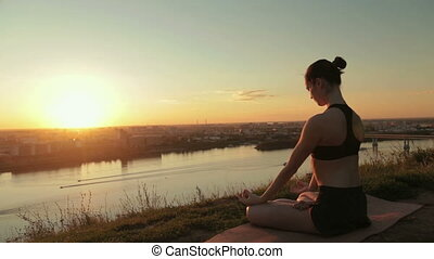 Sporty woman in lotus position in the park at sunset