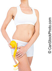 Sporty woman in sportswear holding peeled orange by her thigh