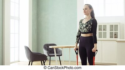 Sporty woman is making squats with sport expander having ...