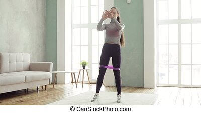 Sporty woman is training making squats and lunges at home in living room.