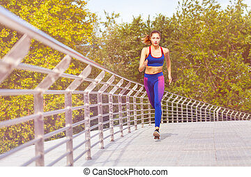 Sporty woman jogging and exercising in the park