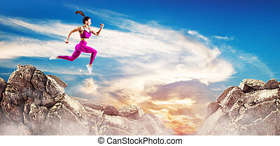 Sporty woman jump through the gap between hills over sky background.