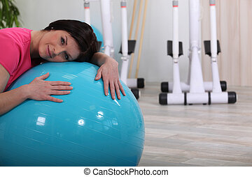 Sporty woman leaning on a fitness balloon