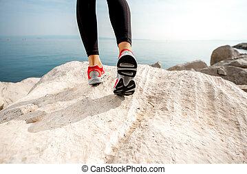 Sporty woman legs on the rocky beach