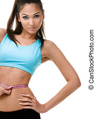 Sporty woman measures her waist