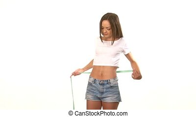Sporty woman measuring her waist and spinning, on white