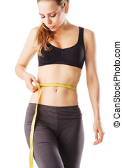 Sporty woman measuring her waist fitness with a tape measure...