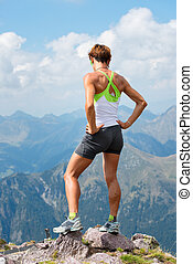 Sporty woman on top of a mountain