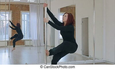 Sporty woman pole dancer makes element on pylon. Slow motion...