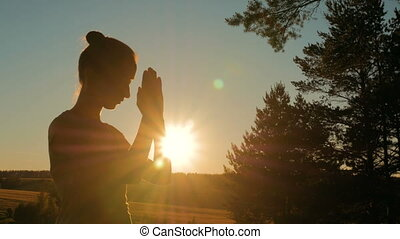 Sporty woman praying in park at sunset - Silhouette of young...