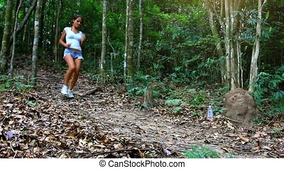 sporty woman running in jungle forest and drinking water. HD. 1920x1080