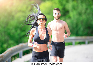 Sporty woman runs in front of her athletic trainer