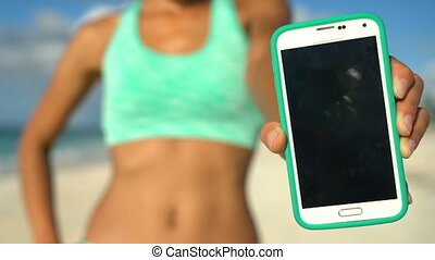 Sporty Woman Showing Smart Phone On Beach - Close up of Smartphone Screen