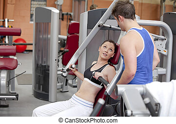 Sporty woman  sitting on a shoulder press talking with her coach in a fitness centre