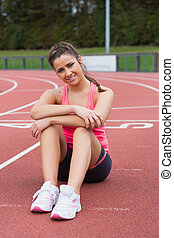 Sporty woman sitting on the running