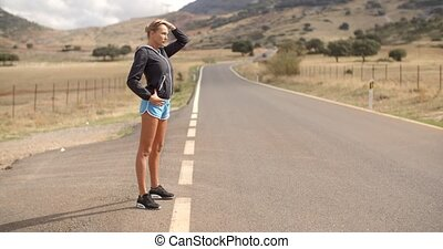 Sporty Woman Standing Alone on the Road