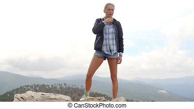 Sporty Woman Standing on Top of Rock