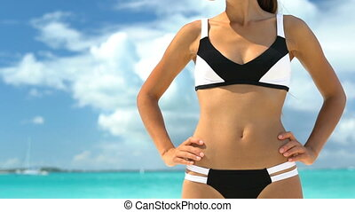 Sporty Woman Standing With Hands On Hip At Beach - Girl Wearing Sunglasses