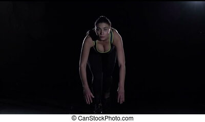 Sporty woman starts running out of darkness in gym, slow...