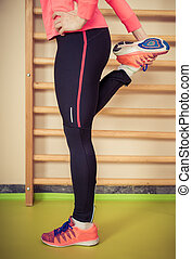 Sporty woman streching in the gym