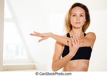 sporty woman stretching hands at yoga class in fitness studio