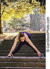sporty woman stretching legs after running