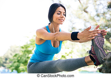 Sporty woman stretching legs in park