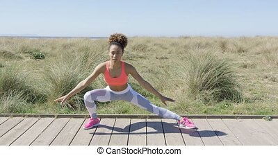 Sporty woman stretching on pavement - Young woman stretching...