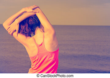 Sporty woman stretching on the beach