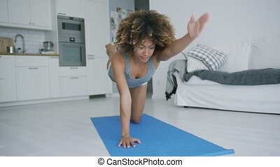 Sporty woman training at home - Pretty ethnic model doing...