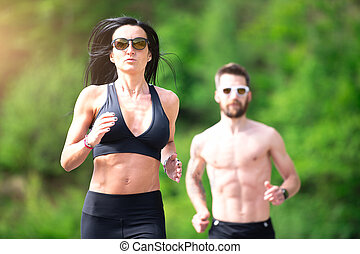 Sporty woman trains in front of her athletic trainer