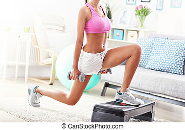 Sporty woman using step platform at home