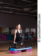 Sporty woman using step platform