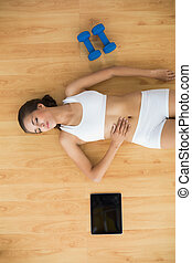 Sporty woman with closed eyes lying next to a tablet and dumbbell