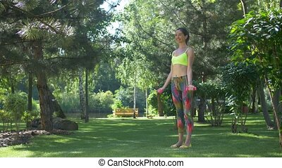 Sporty woman with dumbbells flexing muscles outdoors