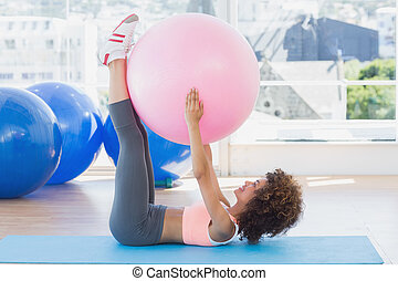 Sporty woman with exercise ball in fitness studio - Side...