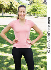 Sporty woman with hands on hips at park - Portrait of sporty...