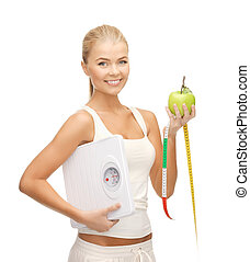 sporty woman with scale, apple and measuring tape -...
