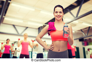 sporty woman with towel and water bottle - sport, exercise...