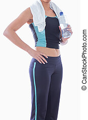 Sporty woman with towel around neck and water bottle
